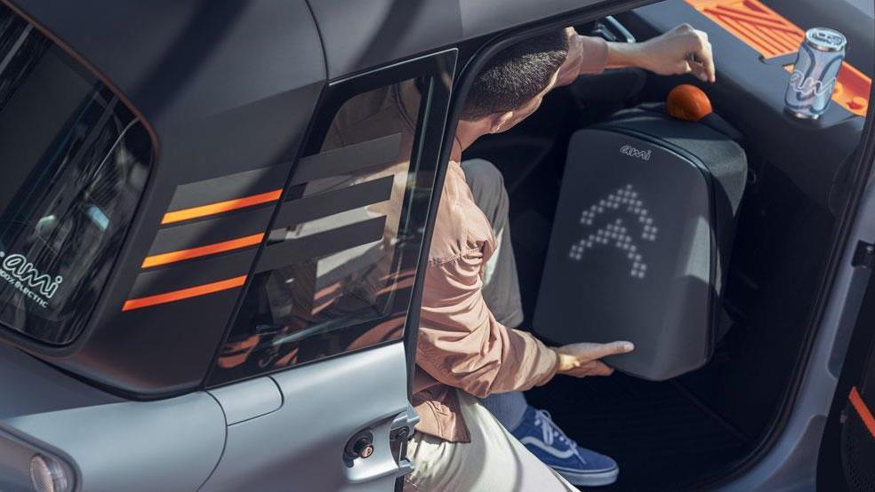 Pasajero colocando la maleta en el espacio creado para depositar maletas dentro del Citroën AMI