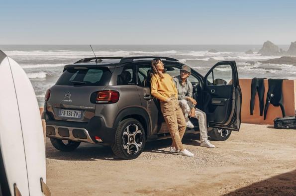 Pareja apoyada sobre el vehículo con el mar de fondo y equipamiento de surf a su alrededor